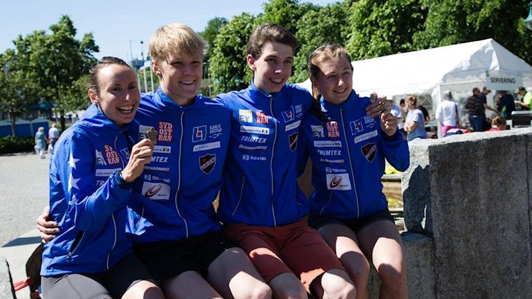 Fyra blåkläda glada idrottare sitter på en bänk och visar upp sina priser.