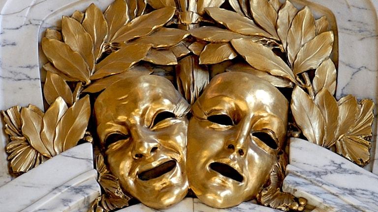 Två teatermasker i guld