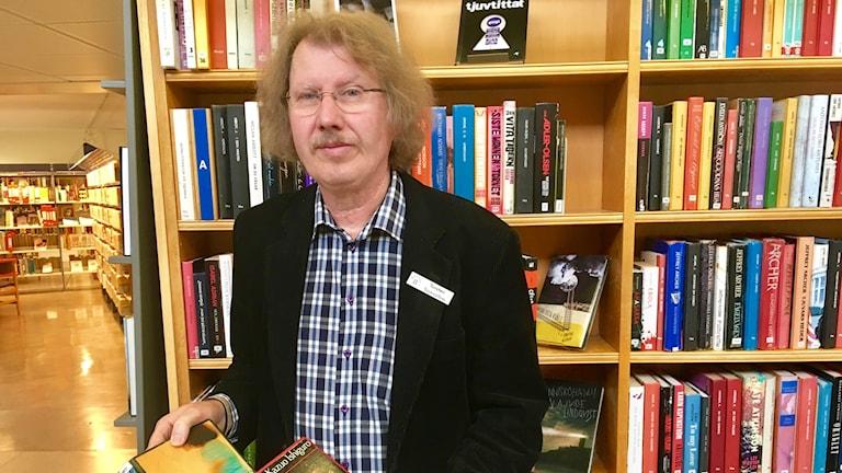 En man håller upp två böcker på ett bibliotek.