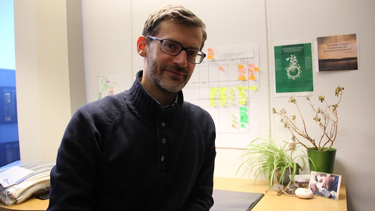 Henrik Ny i sitt arbetsrum. Han har svartbågade glasögon och en stickad mörkblå tröja. Han har en död växt på sitt skrivbord.