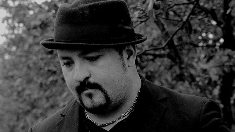 En svartvit bild på Daniel Alfons med hatt.