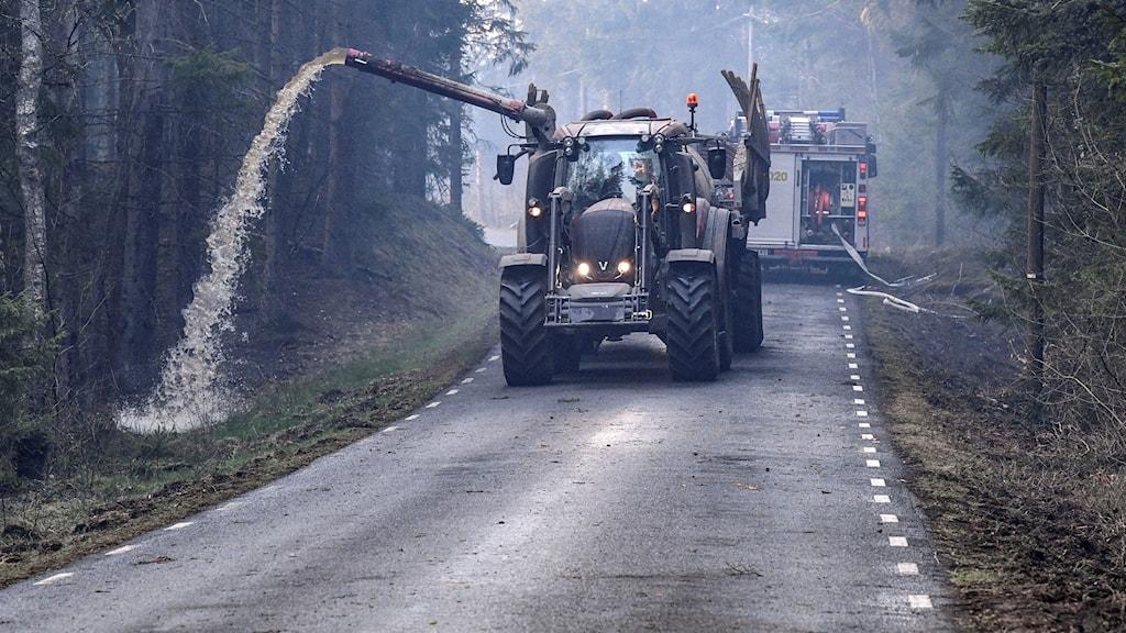Traktor med gödseltank sprutar vatten för att släcka branden i Hästveda