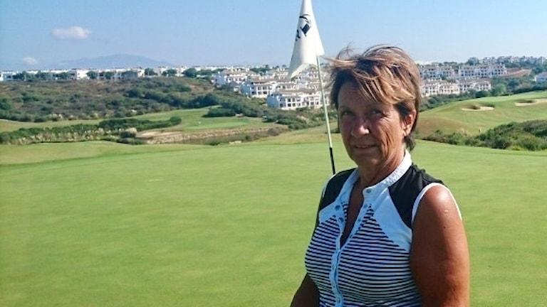 Medelålders kvinna på golfbana