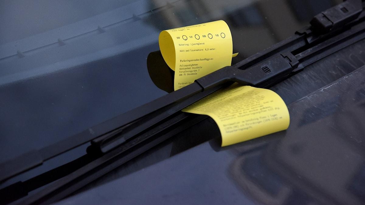 En parkeringsbot under vindrutetorkaren på en bil.
