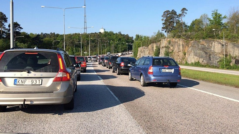 Flera bilar på rad på en motorväg