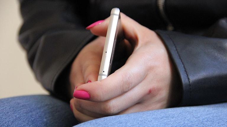 Ett par händer med rosa naglar som håller i en mobiltelefon.