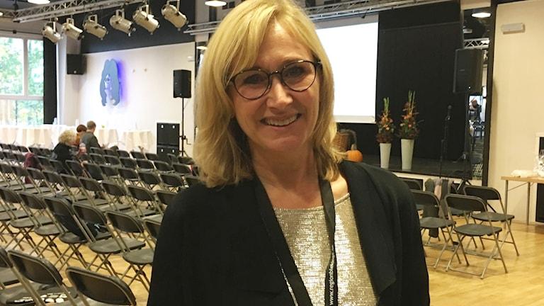Anna-Lena Cederström, regiondirektör, framför ett hav av tomma stolar.