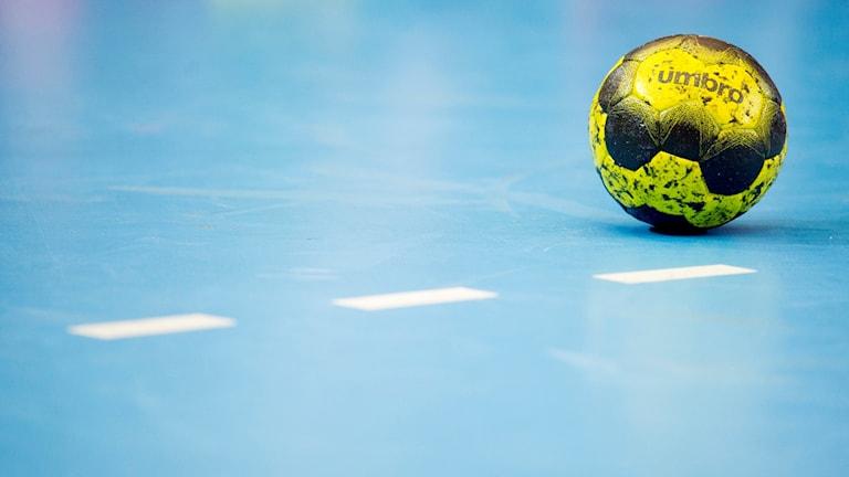 En handboll ligger på ett blått golv.