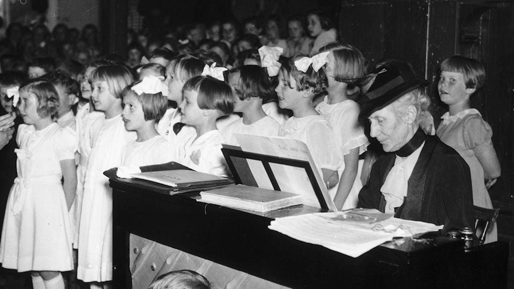 Alice Tegnér sitter vid ett piano och har massa barn omkring sig. Foto:TT
