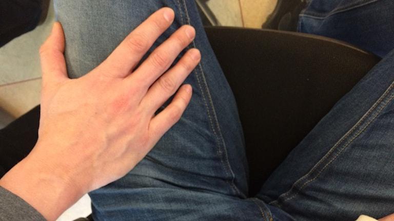En manshand som tafsar på ett ben.