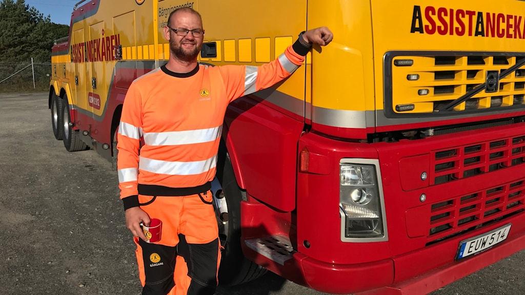 Börgaren Jimmie Persson står med ena armen mot sin stora röd-gula bärgningsbil.