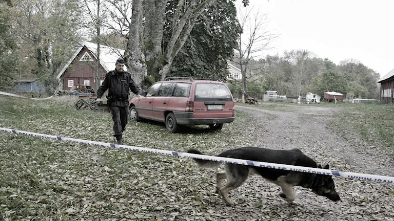 Från platsen för 10 år sedan, polis och hund bakom avspärrningar.