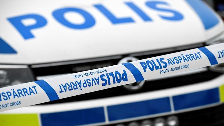 En polisbil vid polisens avspärrningsband.
