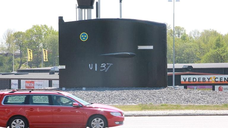 """En bilförare som passerar ubåtstornet i rondellen tittar på klottret """"U137"""" som skrivits på tornet."""