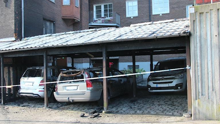 Brandskadade bilar under ett skärmtak. Foto: Mikael Eriksson/Sveriges Radio