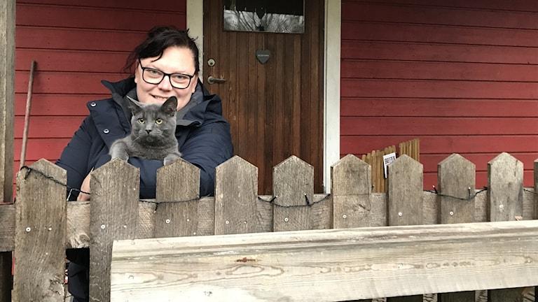 Angelica Svensson med sin katt utanför det röda huset.