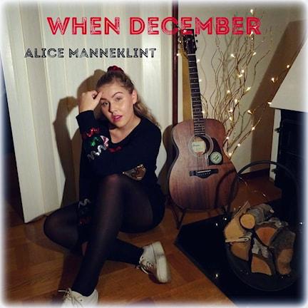 Alice Manneklint sitter på golvet med en gitarr bredvid sig.