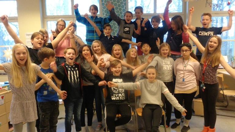 En hel klass med barn på Karlskrona Montessoriskola jublar framför kameran.