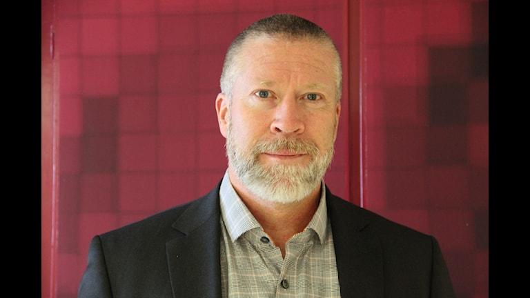 Claes Wiridén, chef för funktionsstödsförvaltningen i Karlskrona, står framför en röd vägg. Endast ansiktet och lite av överkroppen syns.