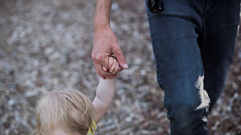 En pappas hand håller en barnhand.