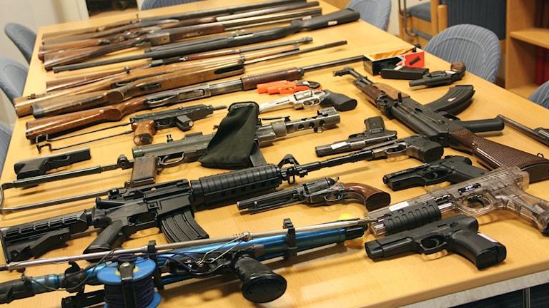 Massor med olika skjutvapen som ligger på ett bord.