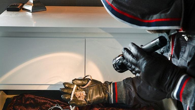 en huvklädd person med ficklampa och handskar tittar i en låda med smycken.