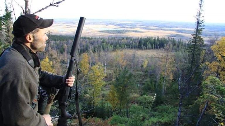 Manollo sitter på en bergstopp med ett jaktgevär i handen