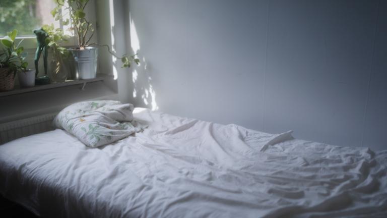 Obäddad säng i en lägenhet.