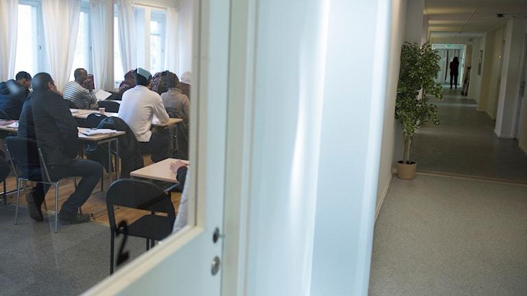 SFI-utbildning pågår bakom en glasdörr