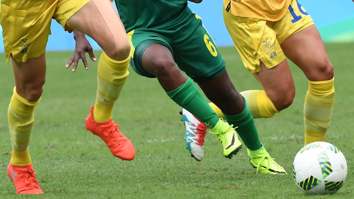 Man ser benen på tre kvinnliga fotbollsspelare som kämpar om bollen.