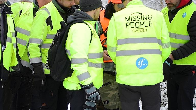 Folk som har samlats med missing peoples västar på sig.