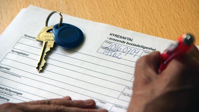En hand som skriver under ett hyreskontrakt.