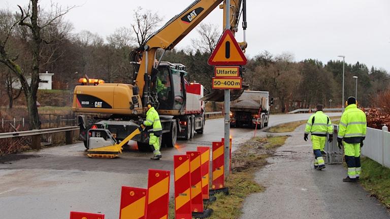 Massa gubbar som arbetar med vägen. Röda varningskoner och en grävmaskin.