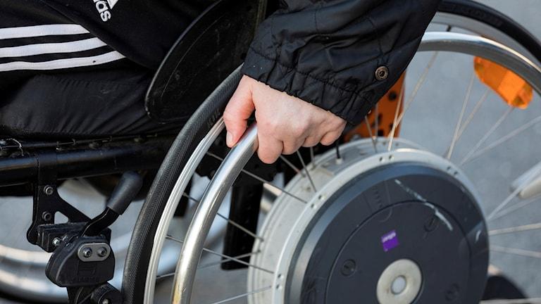 En han håller i ett hjul på en rullstol.