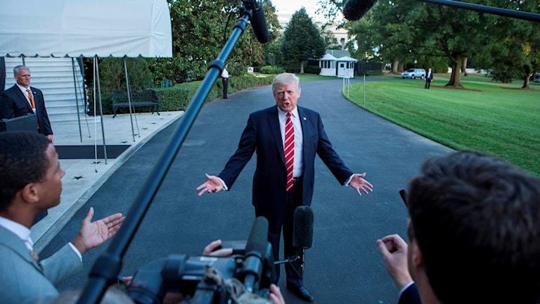 Trump framför journalister.