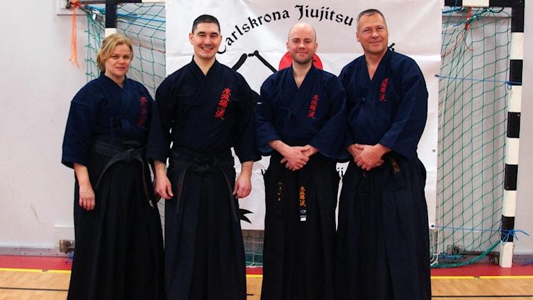 Fyra kampsportsinstruktörer står på rad.