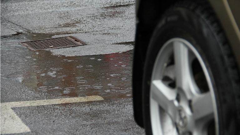 Närbild på en dagvattenbrunn med mycket vatten runtomkring. I förgrunden syns ett bildäck.