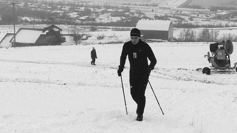 En man med gångstavar går i en snöig backe.