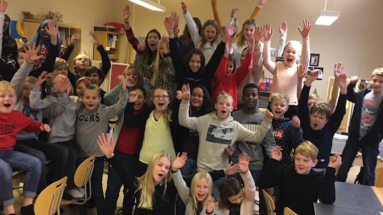 Massor med barn på¨Möllebacksskolan håller upp händerna i luften.