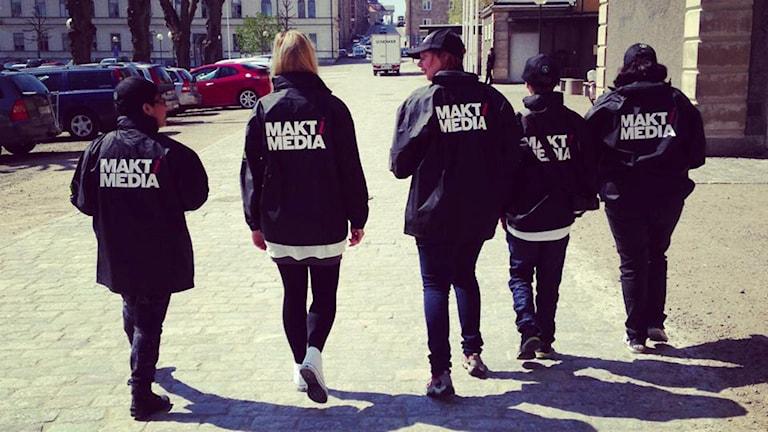 """Fem personer med svarta jackor där det står """"Makt i Media"""" på ryggen."""