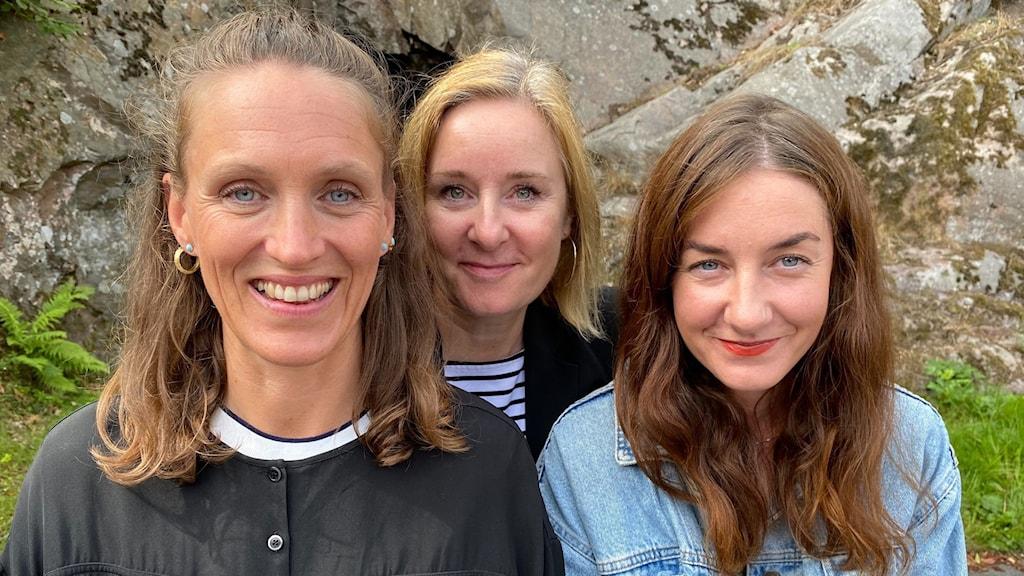 Närbild på tre kvinnor som står nära varandra.  Dom ler och står utomhus framför en bergshäll.