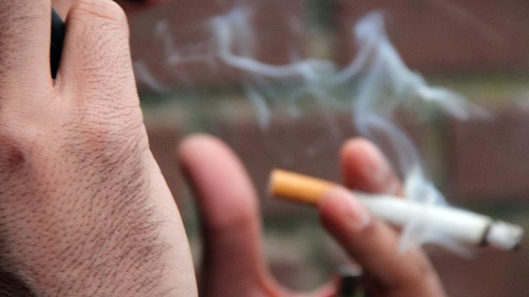 En hand som håller i en cigarett.