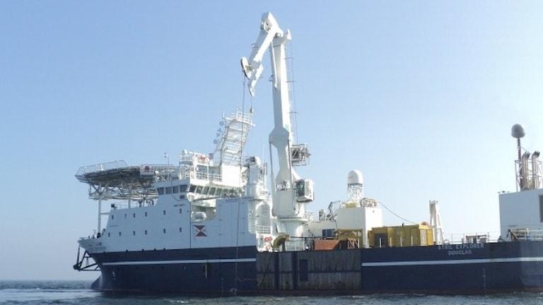 Ett stort fartyg med en lyftkran ombord.