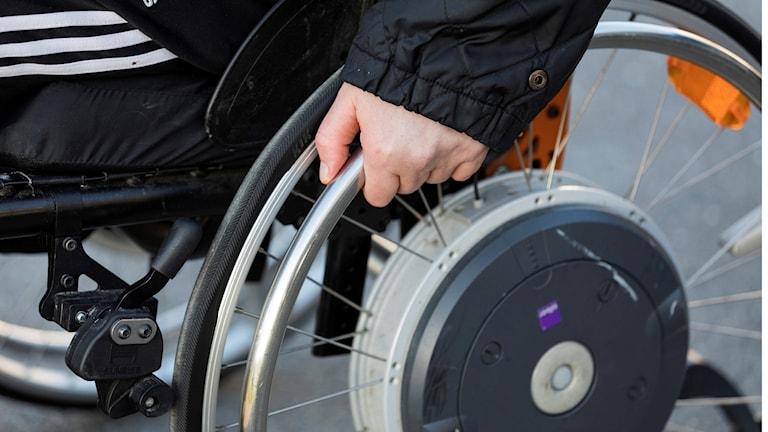 En hand på hjulet på en rullstol.