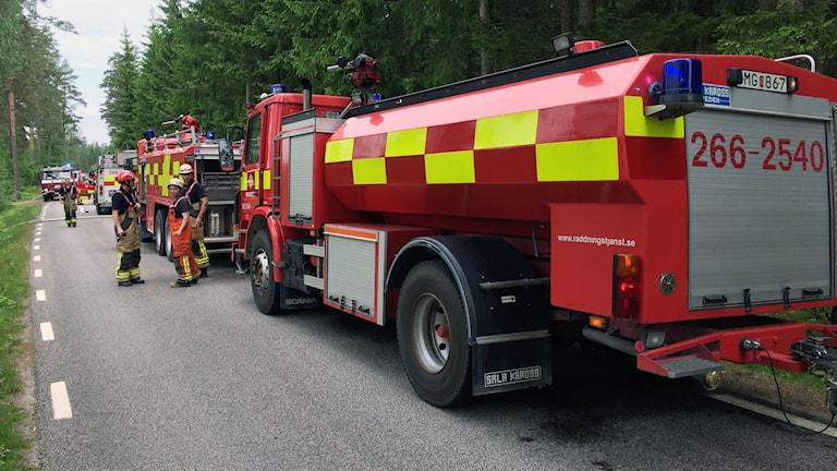 Flera räddningsfordon på rad vid en gräsbrand i Ronneby.