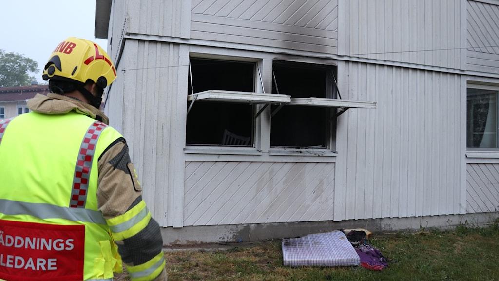 En räddningsledare står utanför två öppna fönster på markplan där elden har gjort sotmärken på fasaden.