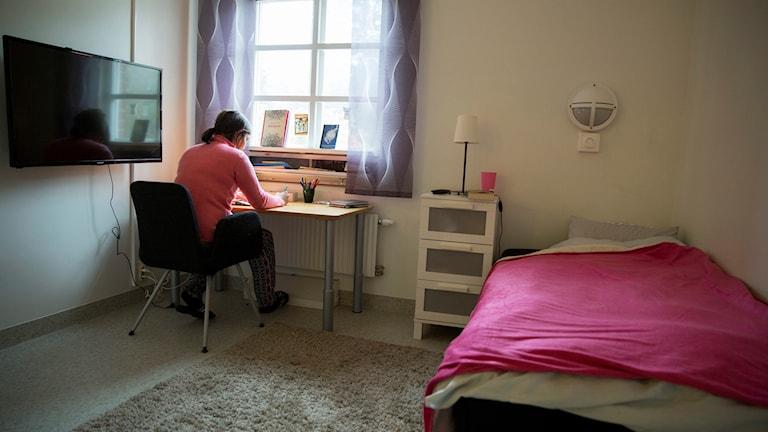 En bild tagen på ett LVM-hem där en kvinna sitter lutad över ett skrivbord.