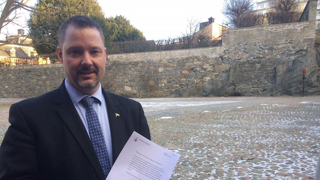 Sverigedemokraternas gruppledare i Karlskrona Christopher Larsson håller domen i handen.