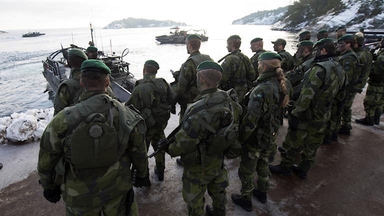 Flera militärer står vid en havsvik och man ser militärbåtar i bakgrunden.