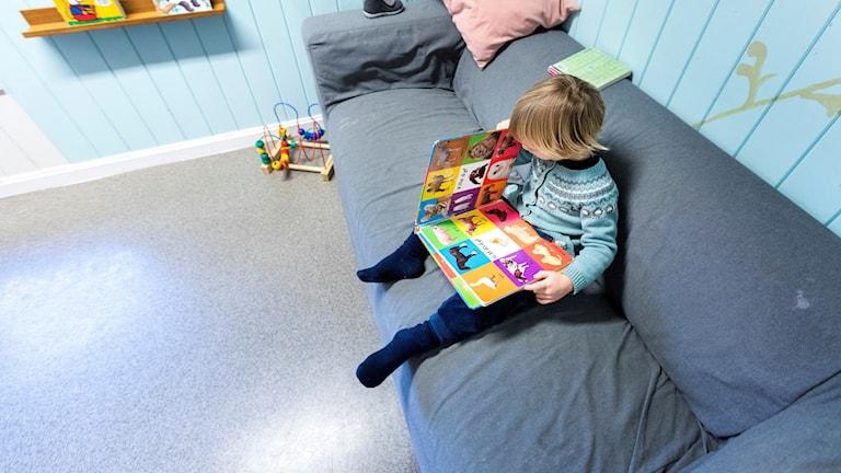 förskolebarn i soffa läser bok